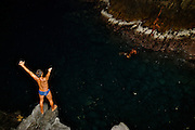 A CLIFF DIVER IS JUMPING FROM  A ROCK CALLED LA QUEBRADA IN ACAPULCO AS PART OF THE SHOW OF EVERY NIGHT.