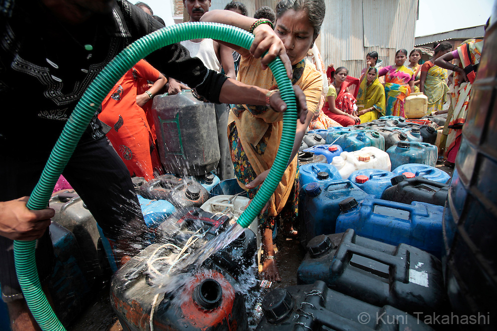 Residents of Govandi neighborhood in Mumbai, India fill water jugs at a community water tank on March 19, 2010. Due to the lack of rain during last year's monsoon, Mumbai is facing one of the worst water shortage in its history and the Municipal Corporation of Greater Mumbai (BMC) has cut 15 % of its water supply in March. Photo by Kuni Takahashi
