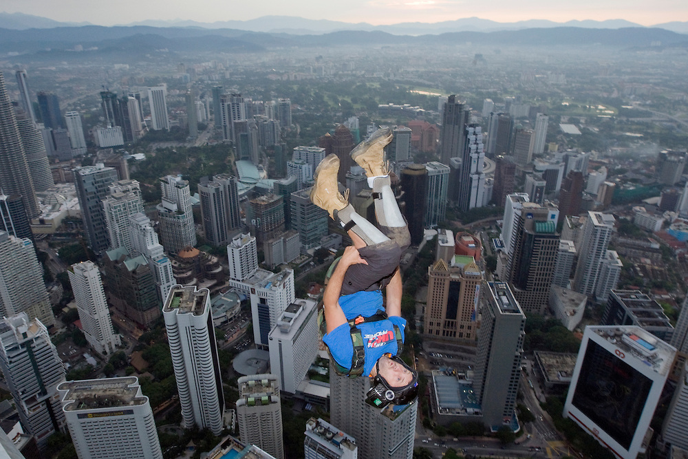 Against the skyline of Kuala Lumpur city, BASE jumper dive from the open deck of Kuala Lumpur Tower (421 metres) during an attempt to set a new record in 24 hours in Kuala Lumpur, Malaysia 29 October 2008. Heavy rain has foiled an attempt to rewrite the world record for endurance BASE jumping in 24 hours at the 421-metre high KL Tower. The group, comprising jumpers from Canada, China, Denmark, Holland, India, Indonesia, Ireland, Italy, Malaysia, New Zealand, Norway, Russia, Singapore, and Turkey, managed 543 jumps, 33 short of the world record of 576 as per the Guinness Book of World Records.BASE is an acronym for Building, Antennae, Span, Earth, and thus represents the fixed-objects from which BASE jumps are made.The jumper must allow a free fall of about three seconds to clear the tower-head section before deploying their chute.From a height of 300 metres, without a parachute, it takes only 10 - 12 seconds to reach the ground.