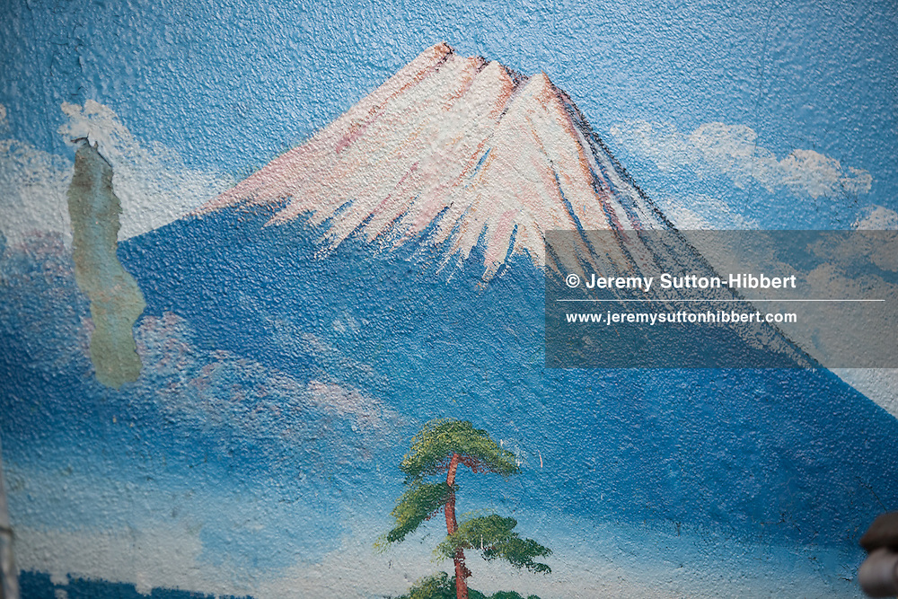 The old painting of Mount Fuji, by painter Hayakawa Toshimitsu, which Penki-e (painter who uses paints) Morio Nakajima, and his apprentice of 6 years Mizuki Tanaka, will refresh with a similar view, at the 'Moto No Yu' sento (public bath house) in Shinozaki, in eastern Tokyo, Japan, on Thursday 23rd June 2011. Nakajima-san and Kiyoto Maruyama are the two remaining painters of Mt Fuji murals in the Kanto area of Japan. Nakajima-san currently undertakes approximately 70 such mural assignments a year, and they each cost the sento owners approximately JPY 100,000.  Mizuki Tanaka,  a graduate of art history, has been an apprentice to Nakajima-san for 6 years but has not yet progressed to the level where she is allowed to paint the Mt Fuji itself, at present she paints the other background details of the mural but not the mountain itself.
