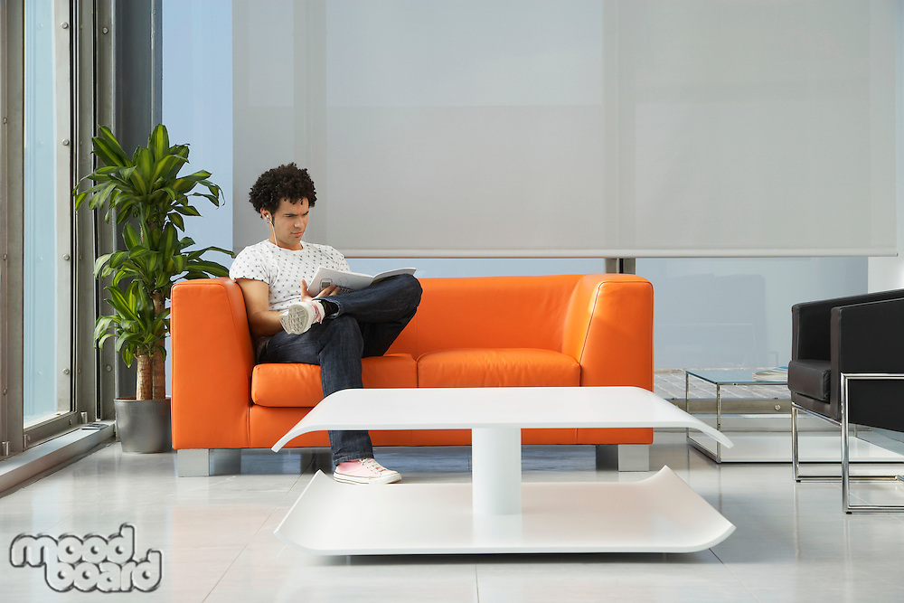 Young man reading newspaper in reception room