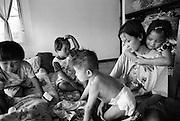 Dai, 27 Jahre alt, HIV-positiv.Pflegemutter in Baan Gerda.Dai mit den Kindern im Schlafraum der Kinder. Alle Kinder sind HIV-positive Waisenkinder...Dream, 5 J. 1v.l. dann Naamson, 3 J., 2v.l. .Dondaan, 3 J. bekommt die Hose an, 3v.l und Dai mit Provinz Lop Buri, Thailand...
