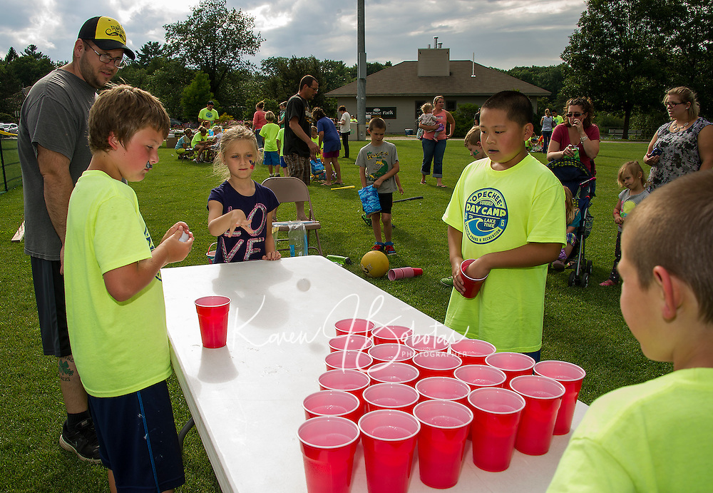 Landen Brothers and Jet Wang operate the Ball Bounce game with Bailey Taggett giving it a try during Laconia Parks and Recs Opechee Peanut Carnival on Thursday evening.  (Karen Bobotas/for the Laconia Daily Sun)