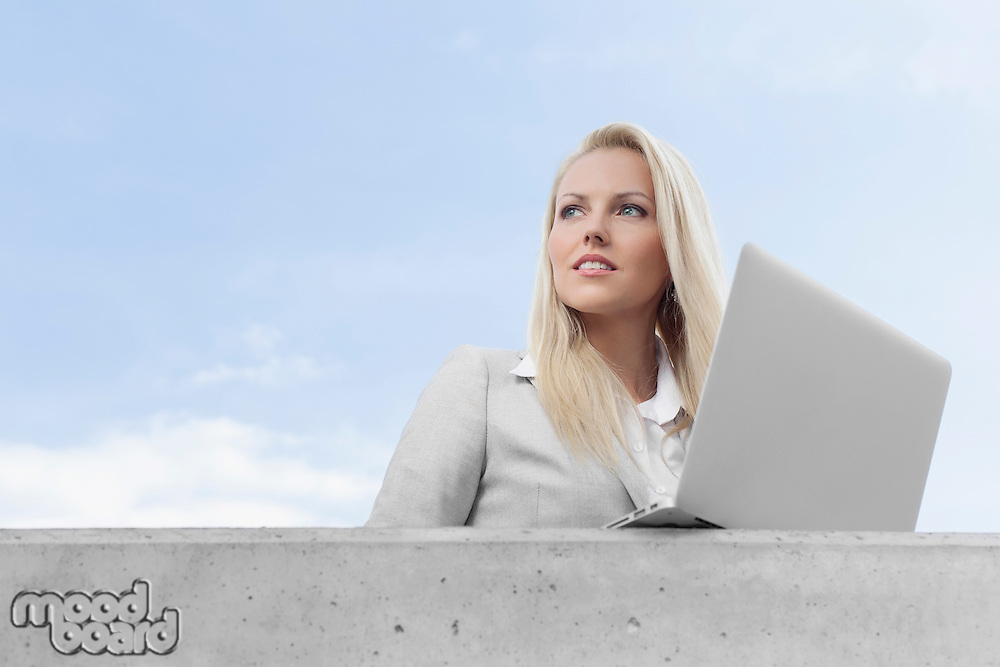 Young businesswoman with laptop looking away on terrace against sky