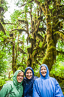 Mother and daughters posing for a portrait in the rain in the Hoh Rainforest, Olympic National Park, Washington, USA.