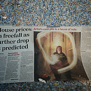 March 27, 2012 - Dublin, Ireland: A newspaper clipping on display at the Billion Euro House art installation by the Irish artist Frank Buckley. ..Worthless euros, taken out of circulation and shredded by Irelands Central Bank, formes the interior walls of an apartment that Mr. Buckley does not own in a building left vacant by the countrys economic ruin...The artist decided to call the apartment  built from thousands of bricks of shredded, decommissioned cash (each brick contains, roughly, what used to be 50,000 euros)  the Billion Euro House. He reckons that about 1.4 billion euros actually went into it, but the joke, of course, is that it is worth simultaneously so much and so little...A large gravestone beside the main door, announces that Irish sovereignty died in 2010, the year that the government accepted an international bailout so larded with onerous conditions that the Irish will be paying for it for years to come. (Paulo Nunes dos Santos/Polaris)