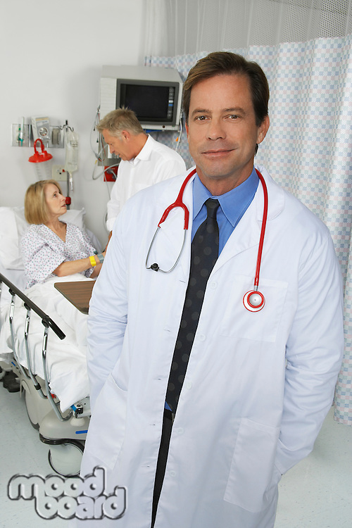 Portrait of doctor in hospital room, patient in background