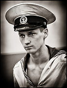 B&W portrait of a young man, sailor at the Russian sailing vessel Mir, staring to the left on Sail Amsterdam, The Netherlands. He is wearing a big hat.