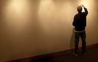 a man applies spackle to a wall to patch holes