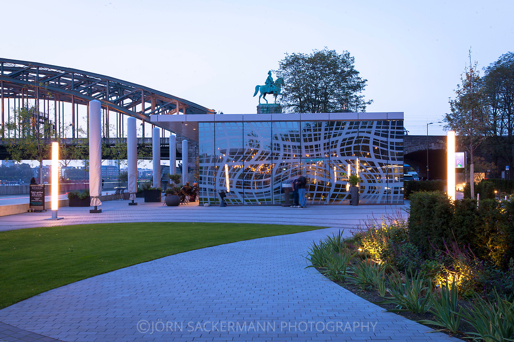 the restaurant Grissini in front of the hotel Hyatt Regency on the banks of the river Rhine in the district Deutz, equestrian statue at the Hohenzollern bridge, Cologne, Germany. The artist Peter Kogler designed the facades with a three-dimensional-looking ornament. It pictures an abstract reflection of the Hohenzollern Bridge on a water surface.<br /> <br /> das Restaurant Grissini vor dem Hotel Hyatt Regency am Rheinufer in Deutz, Reiterstandbild an der Hohenzollernbruecke, Koeln, Deutschland. Der Kuenstler Peter Kogler gestaltete die Fassaden mit einem dreidimensional wirkenden Ornament. Es stellt eine abstrakte Spiegelung der Hohenzollernbruecke auf einer Wasseroberflaeche dar.