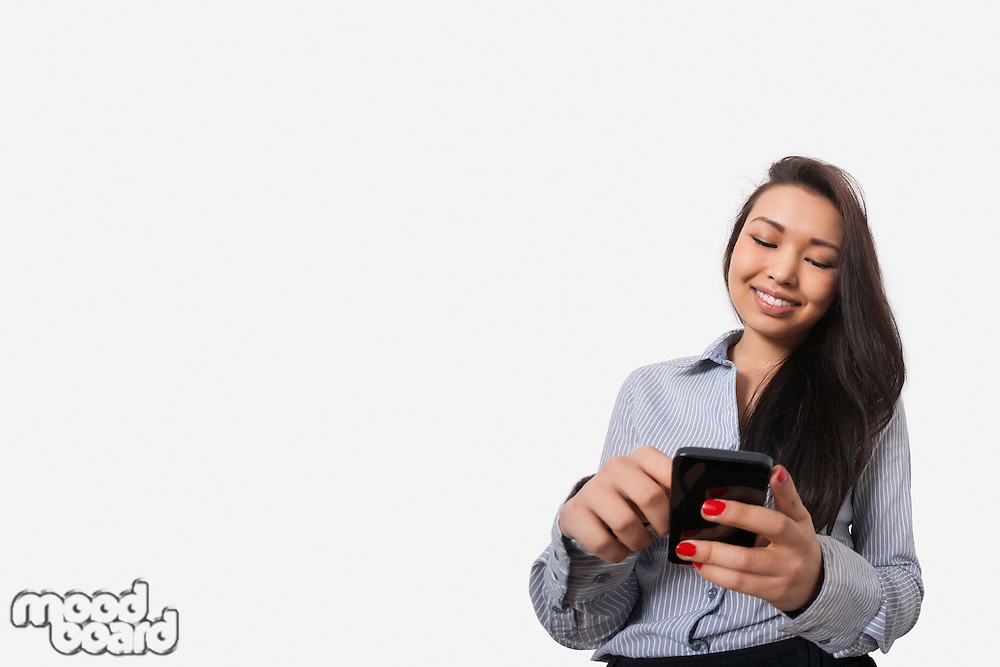Happy businesswoman text messaging through smart phone against gray background