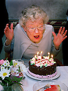 """staff photo by Phil Grout..Mrs. """"Howard"""" W. Hubbard of Edenwald, Towson, rears back and gets.ready to blow out her birthday candles during a celebration of her.86th birthday following dinner last Friday.   Before her retirement, .""""Howard"""" was employed by the Enoch-Pratt Library."""