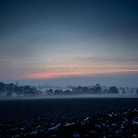 Mist lying low over fields in Suffolk countryside