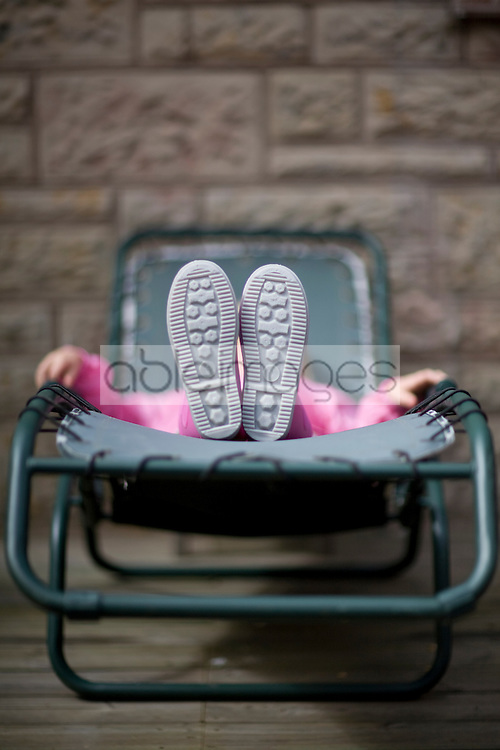Young girl lying on back on sunlounger