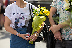 © Licensed to London News Pictures. 03/06/2018. London, UK. A woman with flowers and a t-shirt in memory of a lost one watches on as people mark the anniversary of the London Bridge and Borough Market terror attacks. A series of events have taken place throughout the day, including a service of commemoration at Southwark Cathedral, the planting of an olive tree in the Cathedral grounds, a minute's silence at 4:30pm and the laying of flowers.  Photo credit : Tom Nicholson/LNP