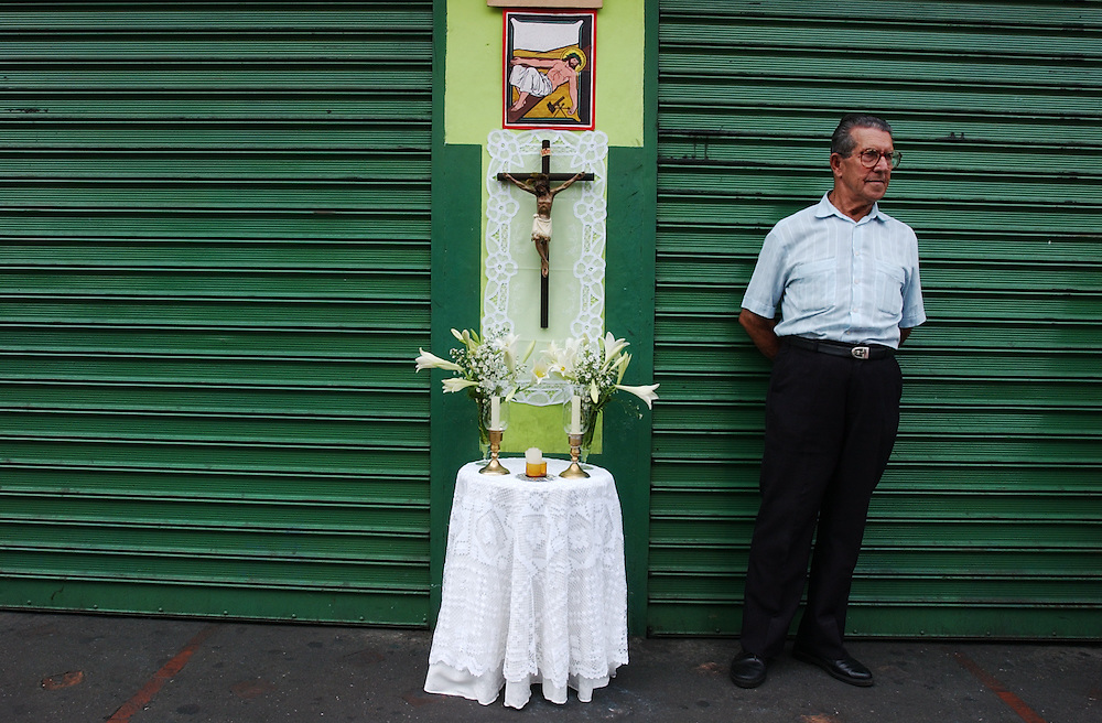 Florencio Rodriguez waits for a relgious procession to pass by on Good Friday.