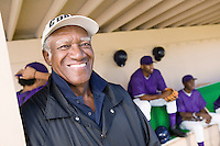 Baseball coach in dugout smiling (portrait)