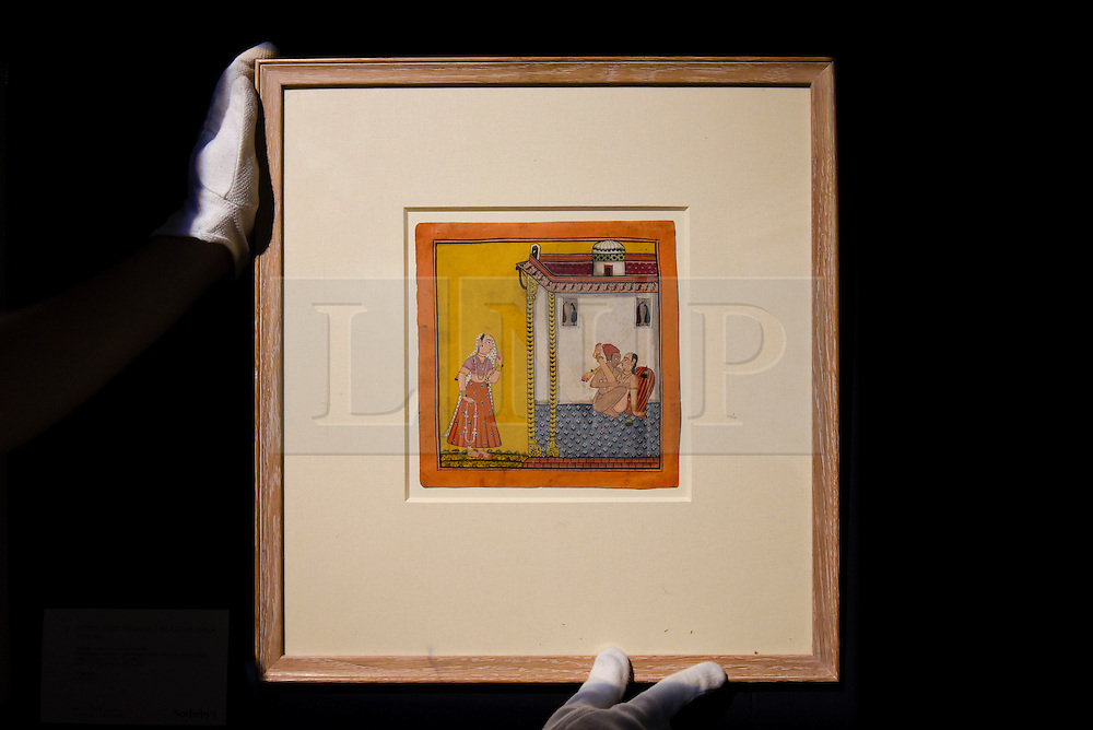 """© Licensed to London News Pictures. 10/02/2017. London, UK.  A technician hangs """"A Loving Couple Watched By A Maiden"""", North India, 1700-40, (est.3-4k), at the preview of the """"Erotic: Passion & Desire"""" sale at Sotheby's in New Bond Street.  The sale, which will take place on 16 February, encompasses representations of love and sex from antiquity to the present day.  Photo credit : Stephen Chung/LNP"""