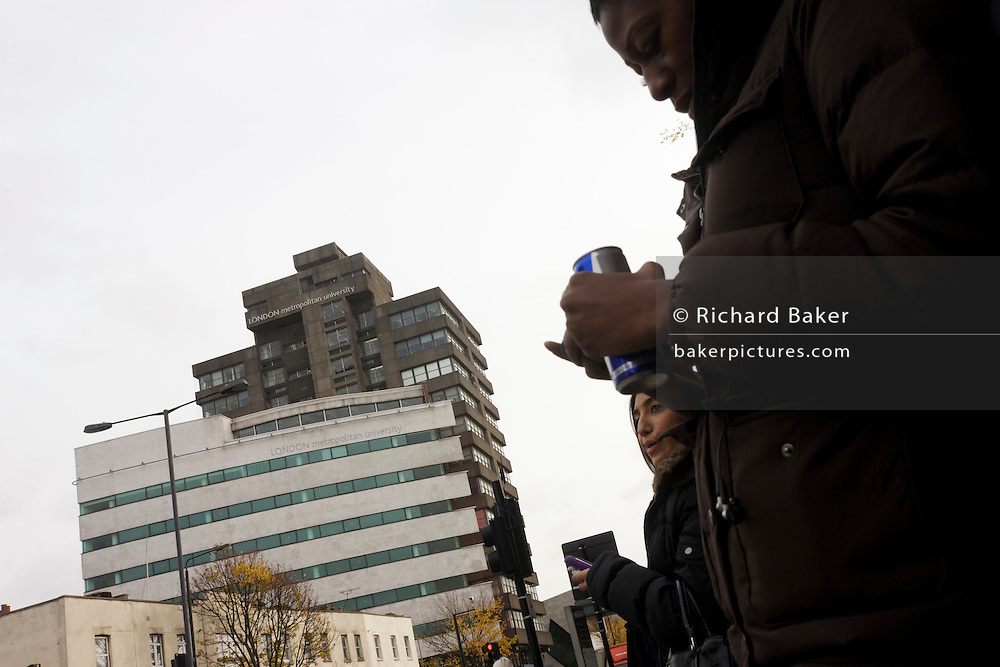 Woman text user outside London Metropolitan University's Holloway Road buildings.