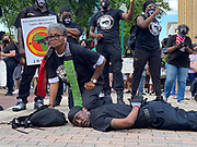 6/6/2020 Jackson MS. <br /> Pictured is Barbara Walker with her knee on the neck of National Black Panther Party Kelvin Bradfield out side the Governor Mansion after a peaceful protest by Black Lives Matter, organized by 18yr old student Maisie Brown. Bradfield chanted ''I can't breathe '' as the crown chanted _check his pulse.''as Walker held her knee on his neck in the 90 degree heat. Photo© Suzi Altman..Student Maisie Brown 18yrs old from Jackson organized a peaceful protest outside the Governors Mansion. She said there voices would be heard and her face would be seen- change is coming. The protest was in honor of George Floyd and in support of ending systematic racism and to end police brutality in Mississippi and America. The National Black Panthers Party from Tupelo Mississippi showed up outside the Governors mansion in the shadow of the State Capitol to protest police brutality. The National Black Panthers Party was their to show their support for change in Mississippi, to end systemic racism and police brutality. Protests have broken out around the world in solidarity to end white supremacy and police brutality. The Panthers showed up at the end of a peaceful protest organized by 18yr old student Maisie Brown. The brutal murder of African American George Floyd by the knee and hands of 4 former Minneapolis Minnesota police officers has sparked a cry for justice and reform around the world. Photo copyright © Suzi Altman<br /> Student Maisie Brown 18yrs old from Jackson organized a peaceful protest outside the Governors Mansion. She said there voices would be heard and her face would be seen- change is coming. The protest was in honor of George Floyd, another Black man killed by the knees and hands of 4 former Minneapolis Minnesota police officers. The protestors are demanding an end to police brutality  and systematic racism among other issues in Mississippi and America. Protests have broken out around the world in solidarity to end white supremacy and police 