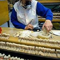 Gluing the felt to the hammers at the Steinway Factory, Astoria, Queens, New York.