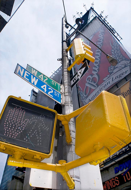 The intersection of New 42nd and W 42nd St in Times Square, New York City, NY. The crosswalk sign has a red hand warning walkers not to cross.