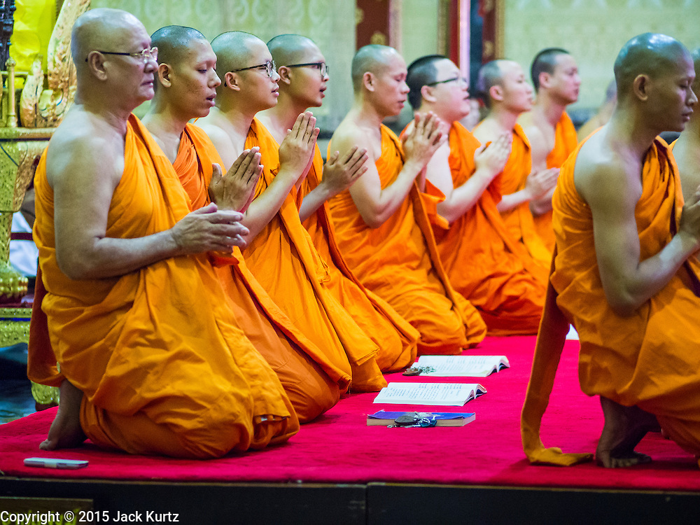 """04 MARCH 2015 - BANGKOK, THAILAND: Buddhist monks pray in the """"wiharn,"""" or prayer hall at Wat Benchamabophit on Makha Bucha Day. Makha Bucha Day is an important Buddhist holy day and public holiday in Thailand, Cambodia, Laos, and Myanmar. Many people go to temples to perform merit-making activities on Makha Bucha Day. Wat Benchamabophit is one of the most popular Buddhist temples in Bangkok.    PHOTO BY JACK KURTZ"""