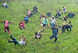 © Licensed to London News Pictures. 28/05/2018. Brockworth, Gloucestershire, UK. The annual custom of Cheese Rolling at Coopers Hill. Participants chase a double Gloucester cheese down a very steep slope with the first to the bottom winning the cheese. The first men's race was won by king of the hill local Chris Anderson who is now the all time cheese rolling champion having won 21 Double Gloucester cheeses over the past 14 years. Photo credit: Simon Chapman/LNP