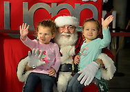 Garden City, New York, USA. November 30, 2013. Twin sisters, Victoria and Venessa, 2 1/2, of Mineola, visit with Santa Claus at the Winter holiday event Festival of Trees, held at Cradle of Aviation Museum, with proceeds benefiting United Cerebral Palsy Association of Nassau County, Long Island.