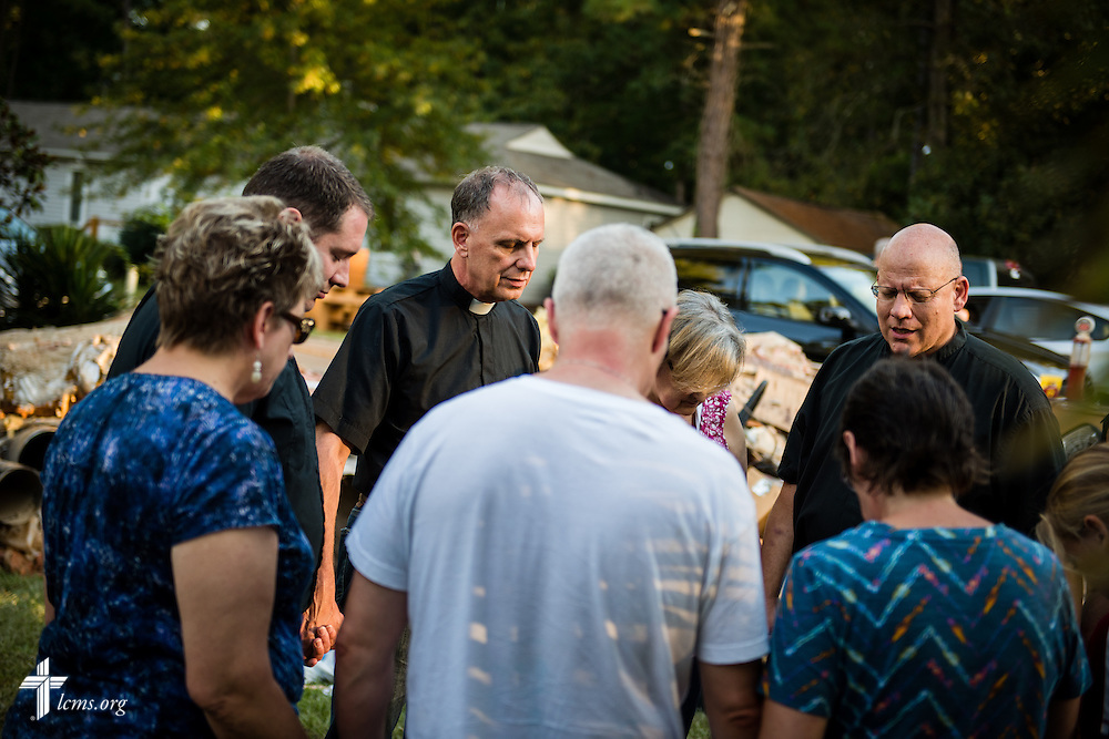 The Rev. Michael Meyer, manager of LCMS Disaster Response (second from left), the Rev. Dr. John R. Denninger, LCMS Southeastern District president, and the Rev. Paul Sizemore (right) of Mount Olive Lutheran Church in Irmo, S.C., pray with residents of a flood-damaged neighborhood on Thursday, Oct. 8, 2015, in Irmo. LCMS Communications/Erik M. Lunsford