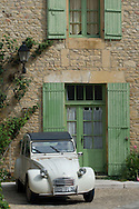 An old Deux Chevaux car parked in front of an old house in a village.  Dordoge, France