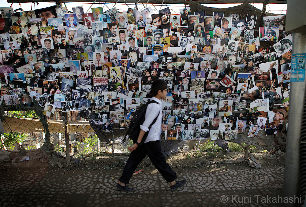 (Kabul Afghanistan - May 17, 2012).A boy walks by a wall of photographs of famous Afghans including kings and politicians in Kabul, Afghanistan. With an estimated population of 30 million, the war-torn country has been struggling to rebuild while political instability continues. .(Photo by Kuni Takahashi)
