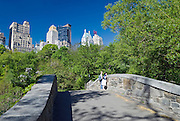 Couple enjoys view of Central Park, New York City in springtime on Gapstow Bridge with view of Midtown Manhattan Skyline.