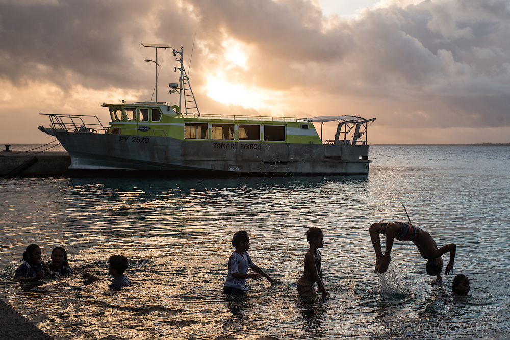 Children plaing in the water at sunset in Rangiroa. On the back one of the boats used to take tourist  to diving spots.