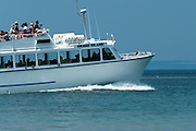 The tour boat, Grand Island, takes its passengers along the shores of Lake Superior, towards the arch at Grand Portal Point
