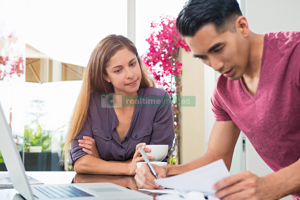Oct. 15, 2014 - Worried couple checking bills and paperwork in dining room (Credit Image: © Image Source/Image Source/ZUMAPRESS.com)
