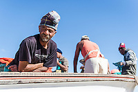 Small-scale commercial fisher resting on his boat, Struisbaai, Western Cape, South Africa