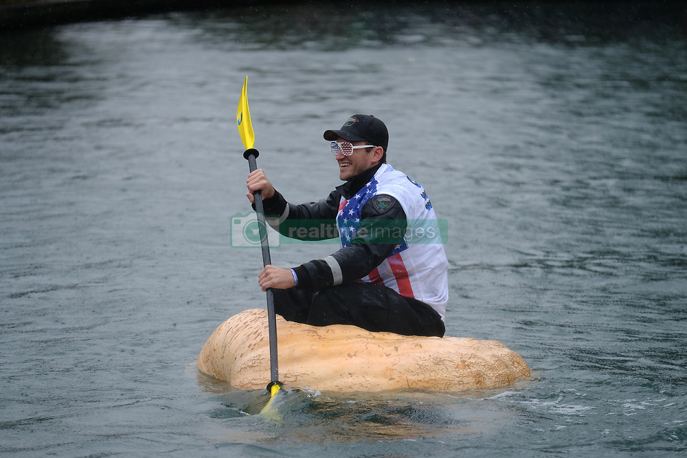 A police officer prepares to race a giant pumpkin across Lake of the Commons at the 14th annual West Coast Giant Pumpkin Regatta in Tualatin, Ore. on October 21, 2017. (Photo by Alex Milan Tracy)