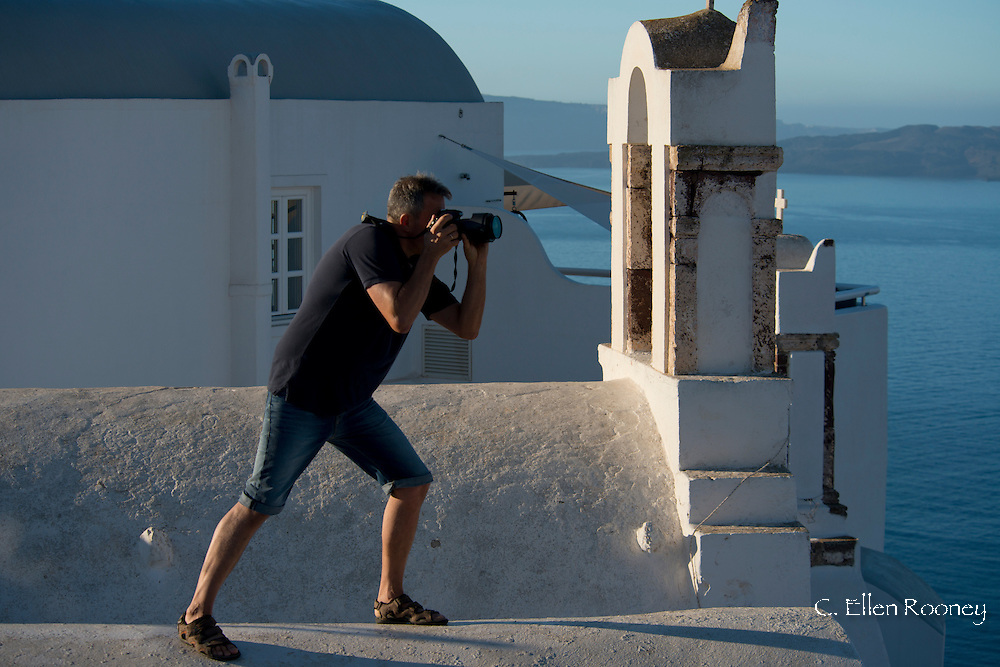 A photographer on the roof of a church photographing the belltower in Oia, Santorini, The Cyclades, The Greek Islands, Greece, Europe