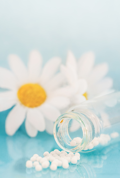 Bottle of homeopathic pills in front of white daisies.