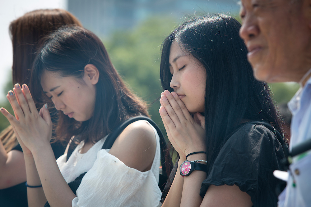 "HIROSHIMA, JAPAN - AUGUST 5 : Visitors pray for the atomic bomb victims in front of the cenotaph ahead of the 71st anniversary of the atomic bombing on Hiroshima at Hiroshima Peace Memorial Park in Hiroshima, western Japan, Friday, August 5, 2016. Japan marked the 71st anniversary of the atomic bombing on Hiroshima. On August 6, 1945, during World War II, the United States dropped a uranium gun-type atomic bomb named ""Little Boy"" on the city of Hiroshima which instantly killed an estimated 80,000 people, tens of thousands more would later die of radiation exposure. Three days later, a second American B-29 bomber dropped a plutonium implosion-type bomb ""Fat Man"" on Nagasaki, killing an estimated 40,000 people.  (Photo: Richard Atrero de Guzman/NURPhoto)"