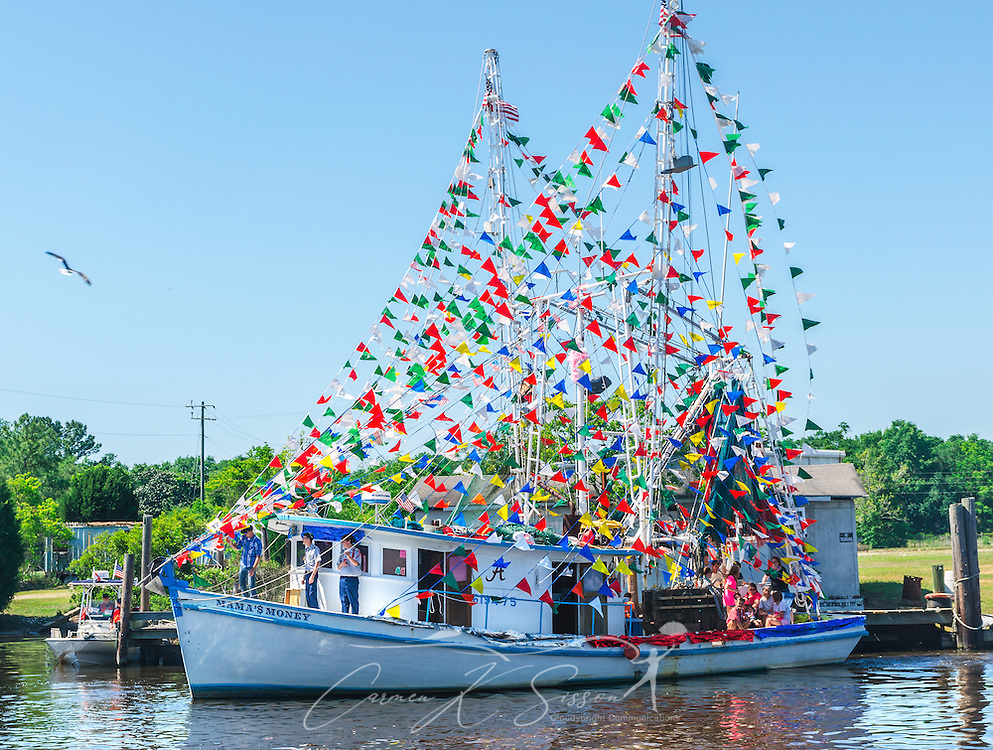 """Mama's Money"" participates in the 65th annual Blessing of the Fleet in Bayou La Batre, Alabama, May 4, 2014. The first fleet blessing was held by St. Margaret's Catholic Church in 1949, carrying on a long European tradition of asking God's favor for a bountiful seafood harvest and protection from the perils of the sea. The highlight of the event is a blessing of the boats by the local Catholic archbishop and the tossing of a ceremonial wreath in memory of those who have lost their lives at sea. The event also includes a land parade and a parade of decorated boats that slowly cruise through the bayou. (Photo by Carmen K. Sisson/Cloudybright)"