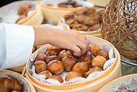 Hands taking bread from a breakfast buffet