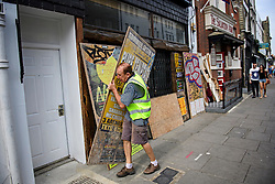 © Licensed to London News Pictures. 25/08/2016. London, UK. A business premises being boarded up in Notting Hill ahead of the annual Notting Hill Carnival which starts this bank holiday weekend. Photo credit: Ben Cawthra/LNP