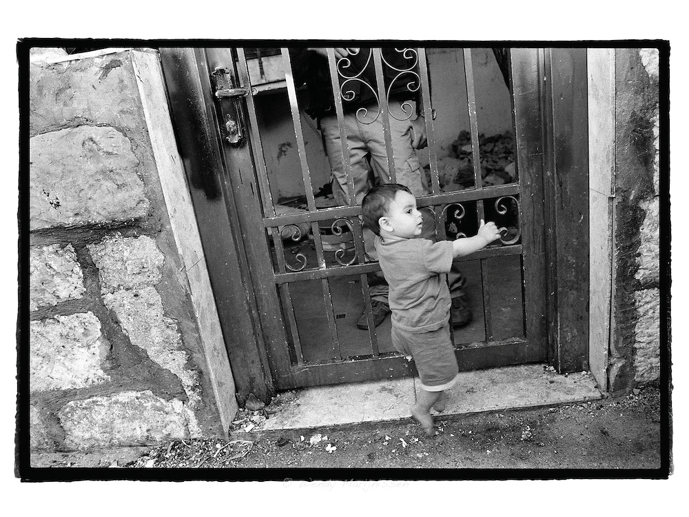 A baby from the al-Ghawi familie is clutching on the gate of his former home, while a security man hired by the settlers guards the house.