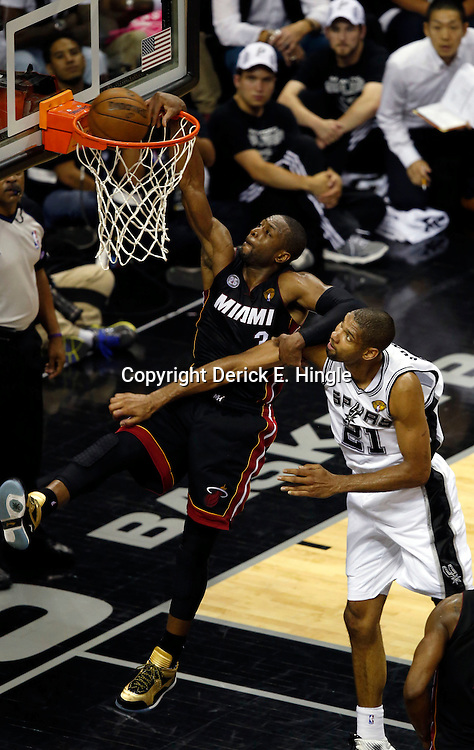 Jun 16, 2013; San Antonio, TX, USA; Miami Heat shooting guard Dwyane Wade (3) dunks against San Antonio Spurs power forward Tim Duncan (21) during the fourth quarter of game five in the 2013 NBA Finals at the AT&T Center. San Antonio Spurs won 114-104. Mandatory Credit: Derick E. Hingle-USA TODAY Sports