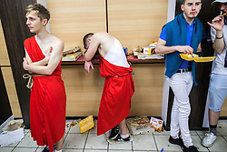 © Licensed to London News Pictures . 27/12/2016 . Wigan , UK . A man slumps against a shelf , surrounded by discarded chicken and pizza in a fast food takeaway . Revellers in Wigan enjoy Boxing Day drinks and clubbing in Wigan Wallgate . In recent years a tradition has been established in which people go out wearing fancy-dress costumes on Boxing Day night . Photo credit : Joel Goodman/LNP