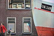 Nederland, Urk, 25-8-2011Een vissersboot ligt op de helling voor onderhoud en reparatie. Een jongetje en zijn moeder komen langsgelopen. Zicht op de haven van dit voormalig eiland.Foto: Flip Franssen/Hollandse Hoogte