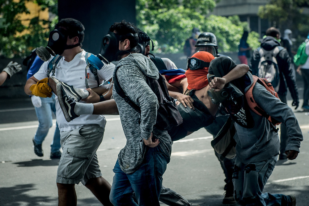 CARACAS, VENEZUELA - APRIL 19, 2017:  Opposition protesters take an injured comrade to safety. Thousands of protesters took to the streets today in Venezuela to show their discontent with the government.  They were met by riot police that fired tear gas and rubber bullets at them.  Some protesters responded by throwing rocks and petrol bombs.  Venezuela is in crisis, and residents face daily struggles over food and medicine shortages, and one of the highest crime rates in the world.  PHOTO: Meridith Kohut
