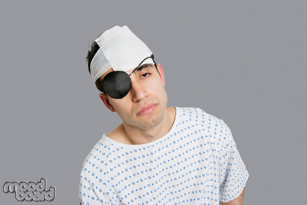 Male patient wearing an eye patch suffering from head injury.